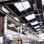 Světlý zářič Schwank pod stropem průmyslové budovy.