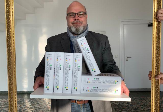 Oliver Schwank hält mehrere Exemplare des Lexikons der deutschen Familienunternehmen.
